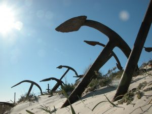 Six rusted anchors, standing in sand.